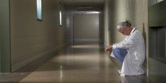 'Female doctor sitting in hospital corridor, side