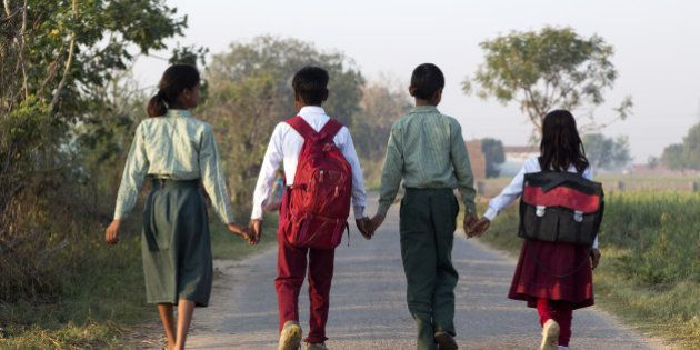 India, Uttar Pradesh, Agra, four young children walking to school hand in hand, back to