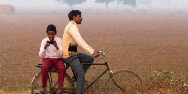 India, Uttar Pradesh, Agra, Indian man riding bike with village boy loking at photos on a