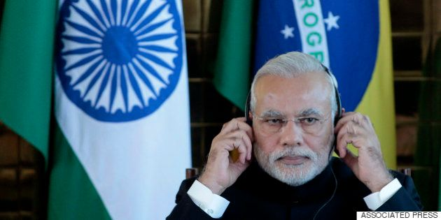 India's Prime Minister Narendra Modi adjusts his headset during a signing ceremony with Brazil's President...