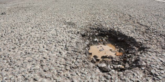 Large deep pothole an example of poor road maintance due to reducing local council repair