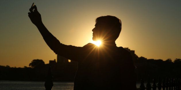 A tourist from Pakistan poses for a 'selfie' photograph as the sun sets in Sydney, Australia, on Tuesday,...