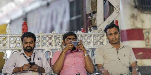 Passengers sit usinmg smartphone at Mumbai Central railway station in Mumbai, India, on Friday, Jan....