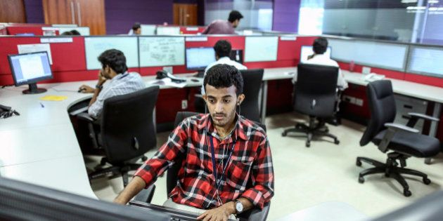 Employees work at their desks in the Tata Consultancy Services Ltd. (TCS) campus in the State Industries...