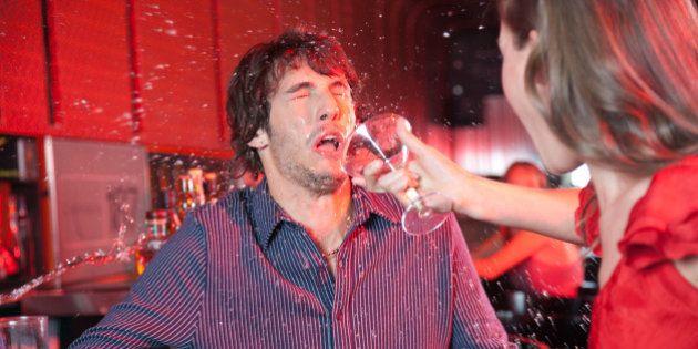 Woman in nightclub throwing beverage in man's