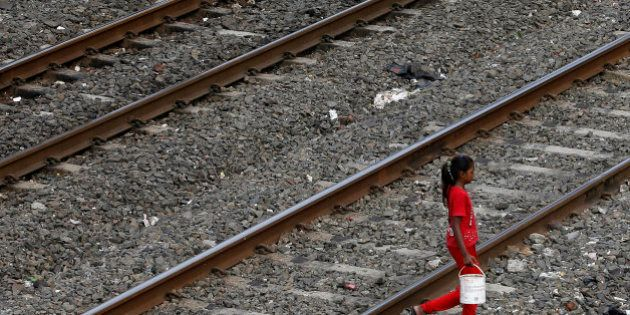 FILE-In this June 30, 2015 file photo,an Indian girl holds a can filled with water and walks past railway...