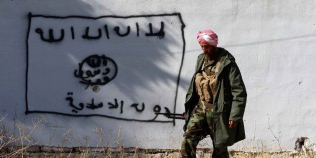 A Kurdish fighter walks by a wall bearing a drawing of the flag of the Islamic State (IS) group in the...