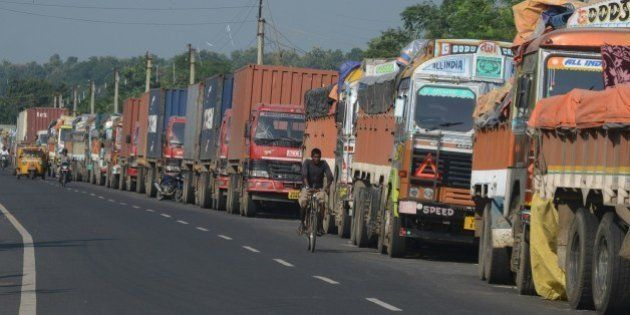 An Indian man cycles past parked Indian trucks carrying goods to Nepal near the India-Nepal border at...