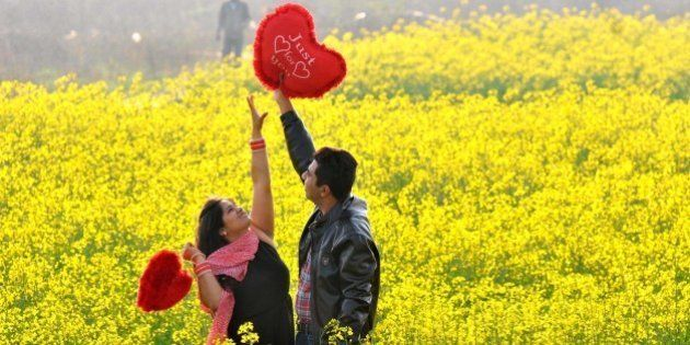 CHANDIGARH, INDIA - FEBRUARY 14: A young couple sharing a light moment in an open field on the outskirts...