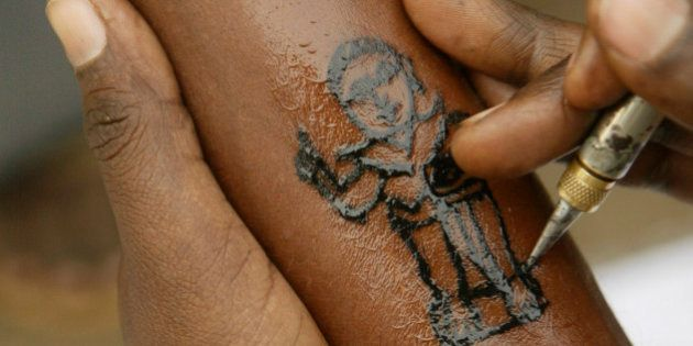 A man gets a tatoo of Bhim Rao Ambedkar, near his memorial in Mumbai, India, Wednesday, Dec. 5, 2007.Ambedkar,...