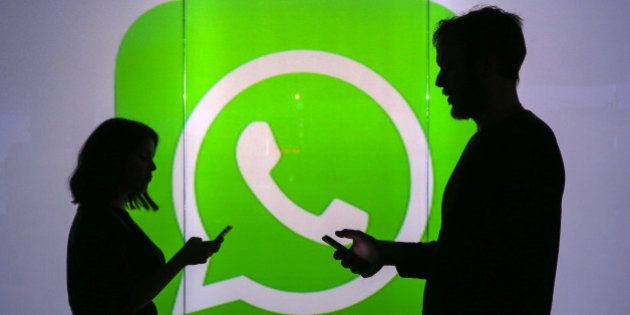 People are seen as silhouettes as they check mobile devices whilst standing against an illuminated wall...