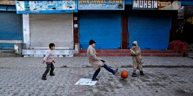 Kashmiri children play soccer at a closed market during a strike in Srinagar, India, Monday, Feb. 9,...