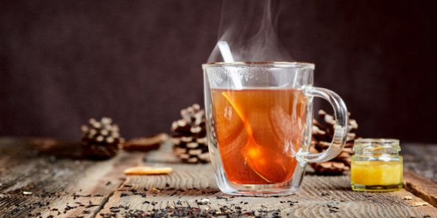 Hot black tea with steam and a little honey pot on a wooden