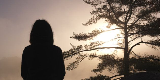 Silhouette of a woman sitting on rocks and facing sunrise sun, tranquil nature scenery, relaxation and...