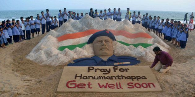 Indian students stand and pray near a sand sculpture created by Sudarsan Pattnaik of Hanumanthappa Koppad,...