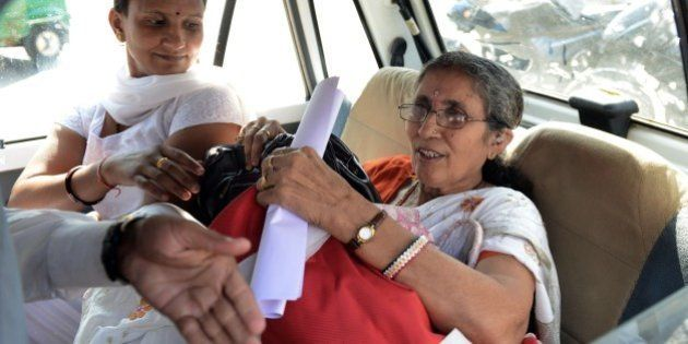 Indian Prime Minister Narendra Modi's wife, Jashodaben (R) holds a copy of the Right To Information (RTI)...