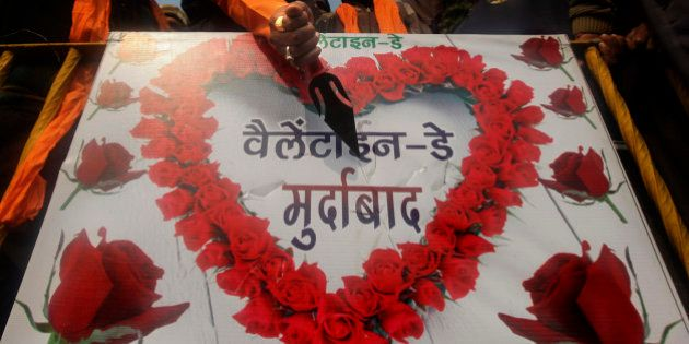 An activist of right wing Shiv Sena pokes a knife into a placard with an anti-valentine's day message...