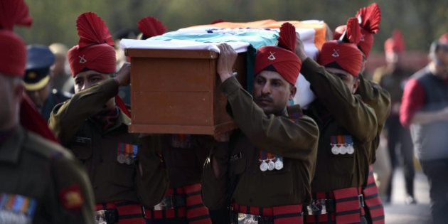 Indian soldiers carry a coffin with the body of avalanche survivor Hanumanthappa Koppad in New Delhi...