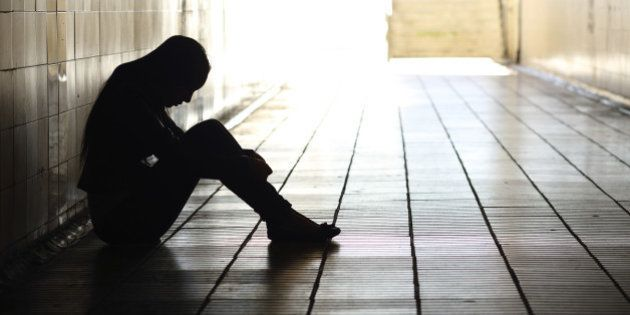 Backlight of a teenager depressed sitting inside a dirty