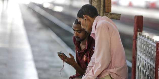 A passenger shows his smartphone screen to another passenger at Mumbai Central railway station in Mumbai,...