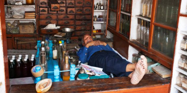 An Indian pharmacist sleeps in his small shop at midday. He is surrounded by cabinets and shelves stocked...