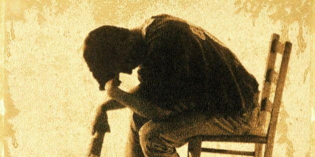 DEPRESSED TEENAGE BOY SITTING HOLDING