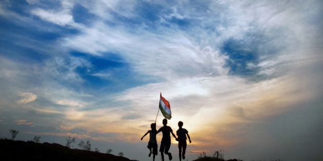 Boys running with indian flag in sunset