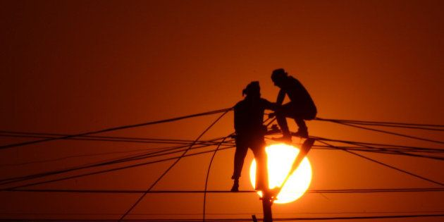 Indian workers adjust electricity cables set up temporarily on the banks of the river Ganga in preparation...