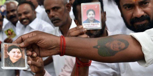 Supporters of India's former southern Tamil Nadu state chief minister J. Jayalalithaa display her photographs...