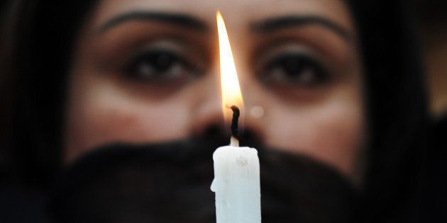 Indian members of a social organisation Our City Our Right holds a candle during a silent protest following...