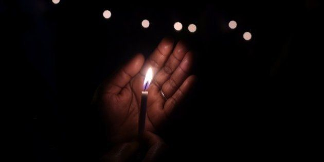 An Indian demonstrator holds a candle as she takes part in a vigil and silent protest against the alleged...