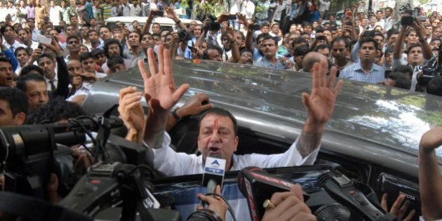 Bollywood star Sanjay Dutt, gestures to the media as he arrives at a court in Mumbai, India, Thursday,...