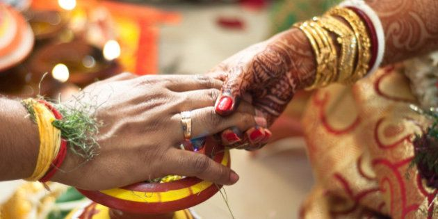 The Bride and the groom holding hands as a part of their wedding ceremony as seen in a traditional Bengali...