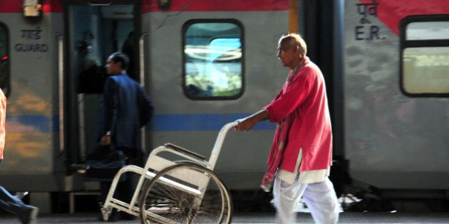 KOLKATA, INDIA - FEBRUARY 24: A porter carrying a wheel chair for assisting passengers at Howrah railway...