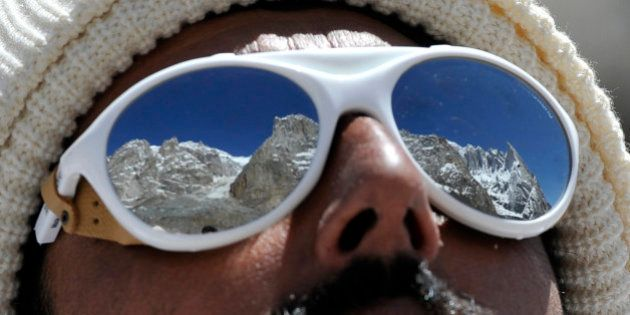 A Pakistani soldier wearing sunglasses looks on at the avalanche site during an ongoing operation at...