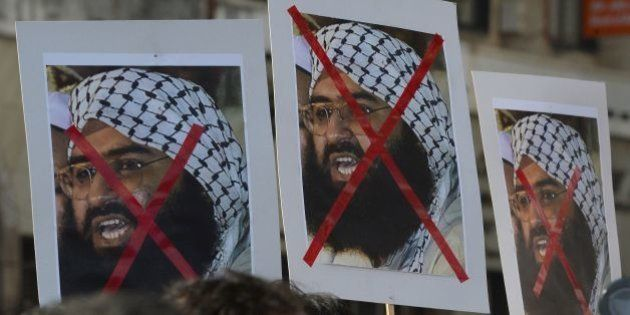 Indian activists carry placards of the chief of Jaish-e-Mohammad, Maulana Masood Azhar during a protest...
