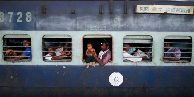 A child sits on the emergency exit window of a train, held by an adult, at a railway station in Puri,...