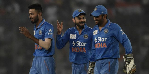 Indian cricketers Hardik Pandya (L) and Virat Kohli (C) and captain Mahendra Singh Dhoni react after...