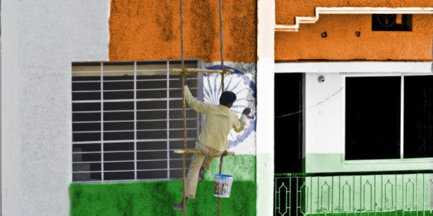 Man coloring pattern of national flag of India on the wall of a building hanging in a rope