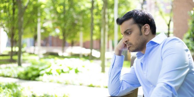 Closeup portrait, stressed young business man, resting face on fist, isolated background of trees outside. Negative human emotion facial expression feelings.