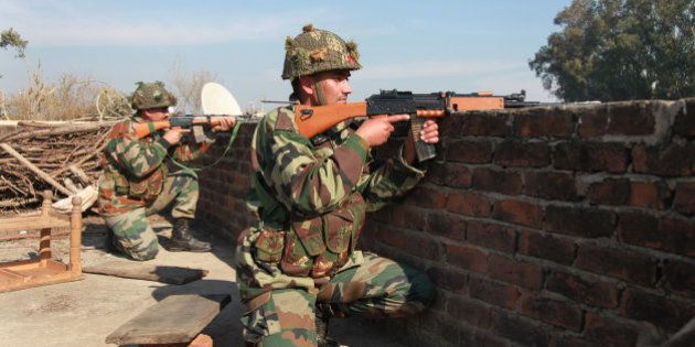 Indian army soldiers take positions on a rooftop of a building outside the Indian airbase in Pathankot,...