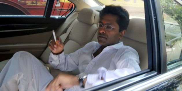 Indian Premier League chief Lalit Modi smokes a cigarette inside his car on his way to meet Mukesh Ambani,...