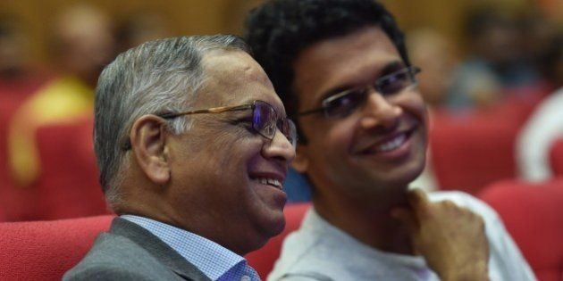 Infosys co-founder Narayana Murthy (L) and his son Rohan Murthy watch the proceedings during the company's...