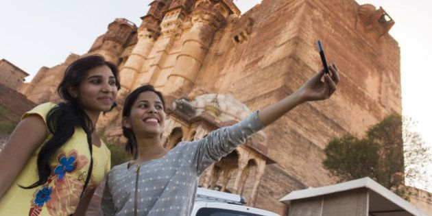 Two girls taking a tourist self portrait or selfie photo on a mobile phone at the Amber