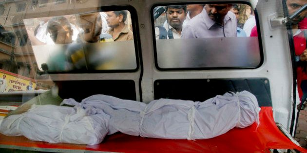 People look at the bodies of two among the victims fatally stabbed by a man as they are kept inside an...