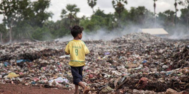 SIEM REAP, CAMBODIA - JUNE 11: A young scavenger wearing a Brazilian national football team t-shirt walks...