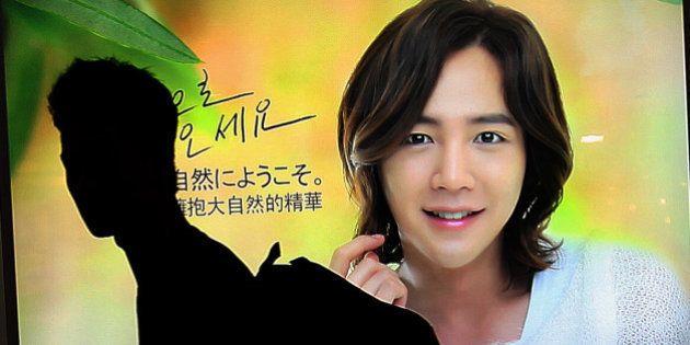 In this Thursday, Sept. 13, 2012 photo, a man walks by an advertisement featuring Jang Keun-suk, a South...