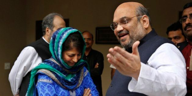 India's ruling Bharatiya Janata Party (BJP) president Amit Shah, right, gestures to the media after a...