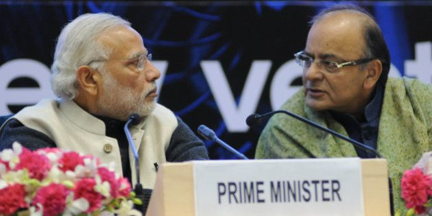 Indian Prime Minister Narendra Modi (L) and Finance Minister Arun Jaitley talk during an event to launch...