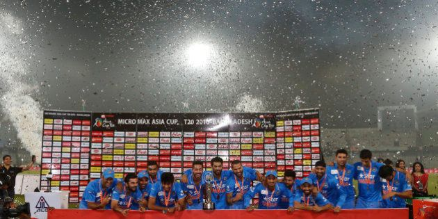 Indian players pose with the trophy after winning the Asia Cup Twenty20 international cricket final match...
